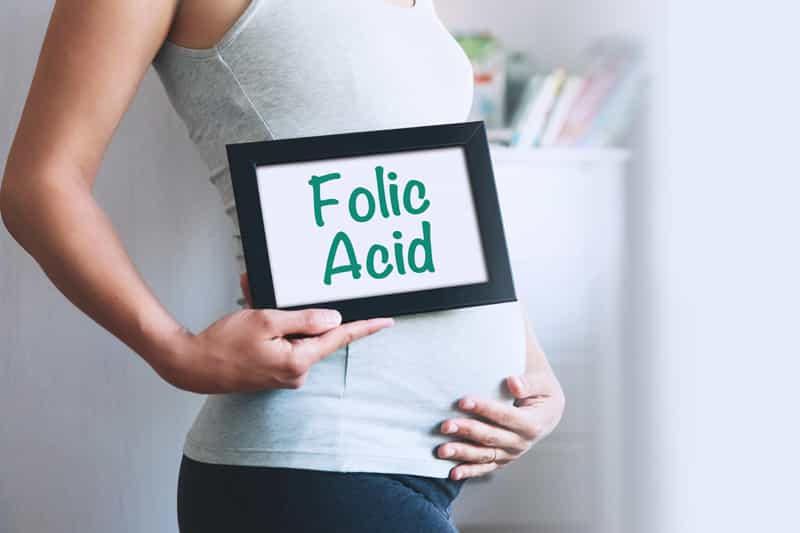 """A pregnant lady holding on to a sign with """"Folic acid"""" written"""