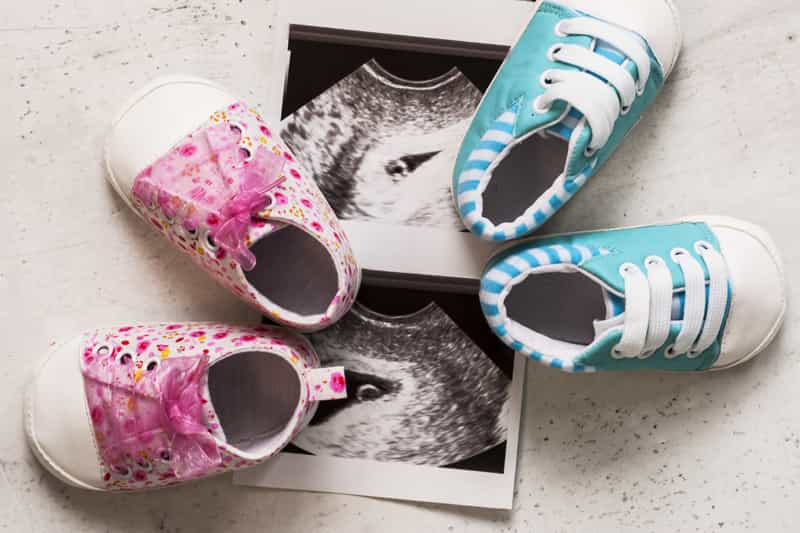 A picture of 2 ultrasound scan with 2 baby shoes