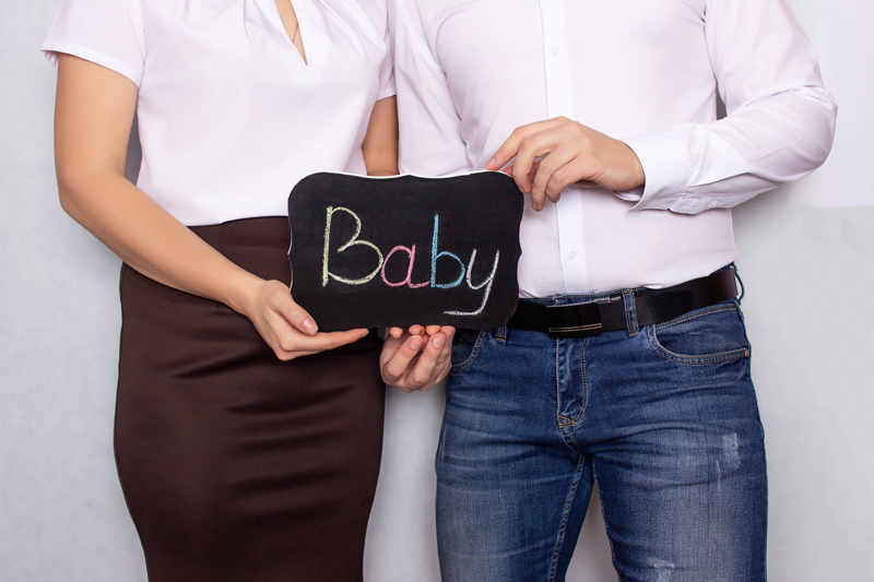 Married couple holding on to a baby sign