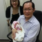 Dr Tan Poh Kok of PK Women's Specialist Clinic carrying a newborn baby at PK Women's Specialist Clinic along with baby's parent