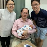 Dr Tan Poh Kok of PK Women's Specialist Clinic carrying a newborn baby at PK Women's Specialist Clinic along with baby's parents