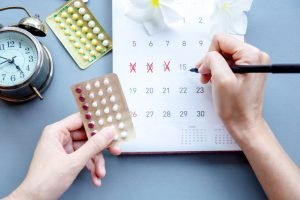 Woman hand holding contraceptive pills and mark the date on calendar